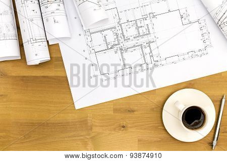 Coffee Cup With Blueprints On Wooden Table