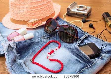 Summer women's accessories: red sunglasses, beads, denim shorts, mobile phone, headphones, a sun hat