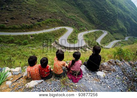 Ethnic minority children sit near amazing mountain pass in Hagiang, Vietnam