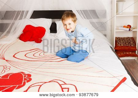 Funny boy plaing on parent's bed