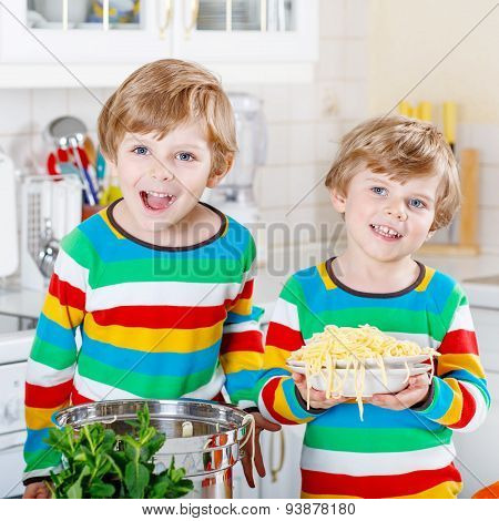 Two Little Kid Boys Eating Spaghetti In Domestic Kitchen.
