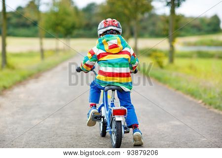 Active Kid Boy In Safety Helmet And Colorful Clothes On Bike