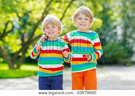 Two Little Kid Boys In Colorful Clothing Walking Hand In Hand
