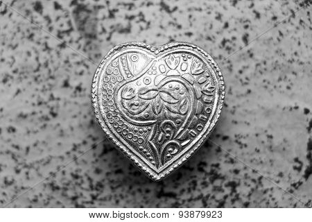 monochrome depiction of antique heart shaped sliver jewelry box kept on a blurred background