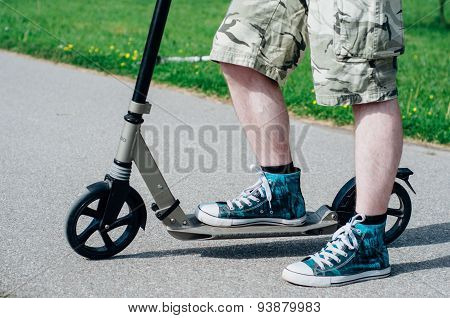 Legs Of Young Man On Kick Scooter