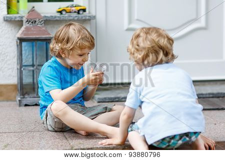 Two Happy Sibling Boys Having Fun Together Outdoors