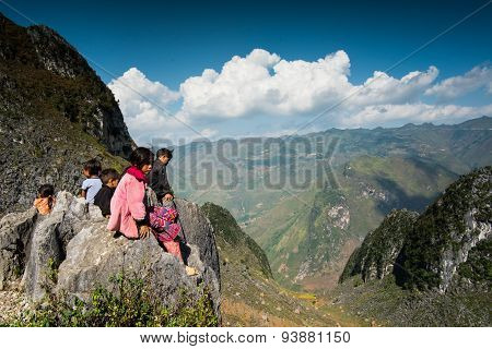 Ethnic minority children sit near mountains in Hagiang, Vietnam