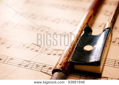 Violin Bow Resting On Sheet Music Composition