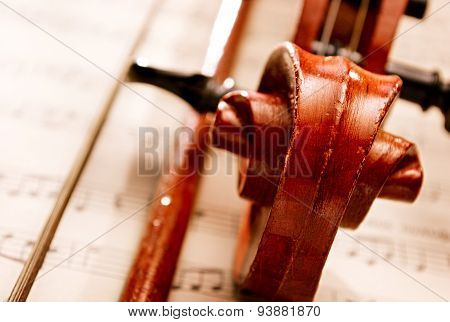 Close Up Of Violin And Bow Resting On Sheet Music