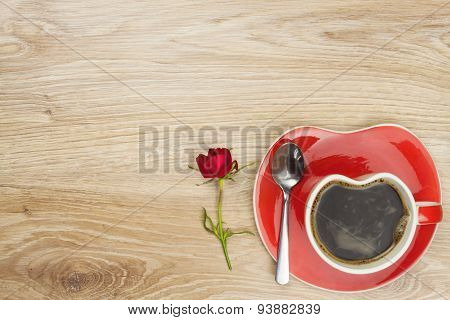 Instant coffee in a cup on a wooden table with a rose. Cooked out of love.