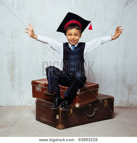 small black boy in  graduation hat sits on the old suitcases and swing hands wants to hug everybody.  instagram toned