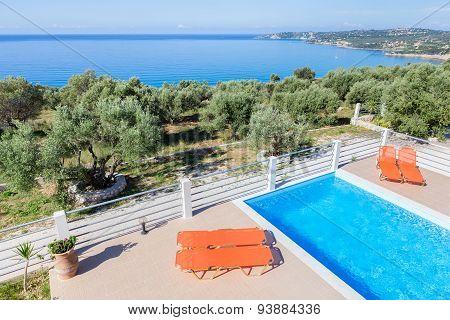 Sun loungers on terrace with swimming pool near sea
