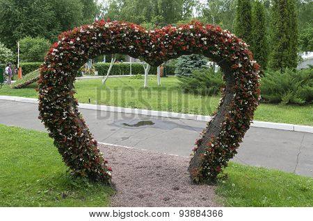 Big Heart (topiary Figure) Of Fresh Flowers In The Park. The Passage To The Alley Through The Heart