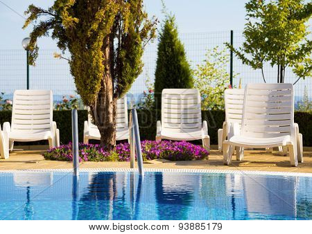 Swimming Pool With Arranged White Sunbeds