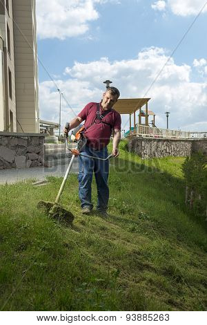 Vertical image of gardener mowing lawn with string lawn trimmer.