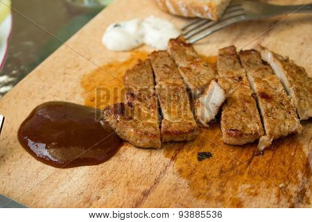 Cut Pork Steak And Bbq Dip On Chopping Board