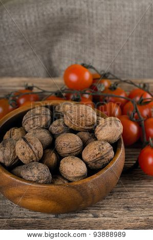 Wooden Bowl Full Of Walnuts And Branch Of Tomatoes