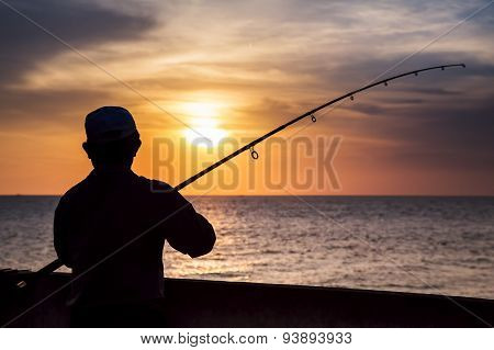 Fisherman Silhouette On The Beach At Colorful Sunset