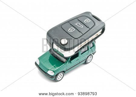 Green Car And Car Keys On White
