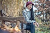 picture of sitting a bench  - Beautiful alone cute girl sitting on bench in a autumn day - JPG