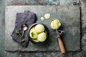 stock photo of mint-green  - Green tea ice cream with mint leaves and Spoon for ice cream on stone slate background - JPG