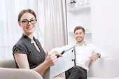 picture of psychologist  - Portrait of a beautiful woman psychologist wearing glasses and black blouse sitting at the light doctor office smiling holding some documents - JPG