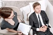 foto of psychologist  - Top view of a psychologist sitting in the armchair holding a clipboard in her hands and looking at her client lying on a couch near relaxing  - JPG
