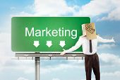 picture of anonymous  - Anonymous businessman with arms out against signpost showing marketing direction - JPG