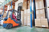 stock photo of forklift driver  - warehouse worker driver in uniform stacking cardboxes by forklift stacker loader - JPG
