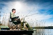pic of jetties  - Man fishing at lake sitting on jetty close to the water - JPG