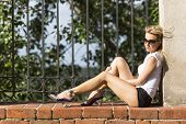 pic of lonely woman  - Young lonely blonde woman in sun glasses and shorts sitting in the Park on a brick wall - JPG