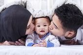 foto of muslim kids  - Portrait of two young muslim parents lying on the bed while kissing their baby under the blanket - JPG