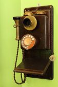 picture of rotary dial telephone  - old classic wood telephone hanging on green wall - JPG