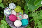 stock photo of gift basket  - Handmade basket of egg Easter symbol traditional culture closeup of egg on green background knit gift from wool to make decorative on holiday - JPG