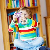 image of daycare  - Active kid boy making photos with photocamera indoors - JPG