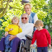 image of grandfather  - Two little kid boys their grandmother and grandfather in wheelchair in summer garden - JPG