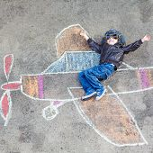 stock photo of creativity  - Happy little kid boy in pilot uniform having fun with airplane picture drawing with colorful chalk - JPG