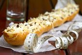 stock photo of baguette  - Baguette with cheese and measure tape on table in restaurant - JPG