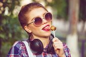 image of lollipop  - Young hipster girl listening to music on headphones in a summer park - JPG