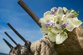 foto of calla  - Wedding bridal bouquet with white callas and blue summer sky - JPG