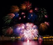 Постер, плакат: Red pink colorful fireworks explode in Malta in dark sky Malta fireworks festival Independence
