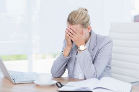 pic of frown  - Frowning businesswoman grasping her head in her office - JPG