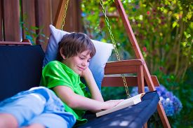 pic of swing  - Happy school boy reading a book in the backyard - JPG