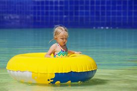 stock photo of inflatable slide  - Funny portrait of cheerful baby girl swimming with fun on yellow tube in aqua park pool - JPG