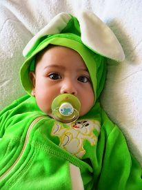 picture of pacifier  - Portrait of a baby boy in a rabbit costume with a pacifier in his mouth on a white towel