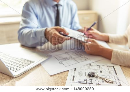 Cropped image of handsome realtor in classic shirt and happy young couple signing documents while sitting in office