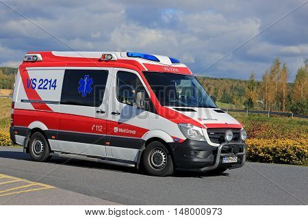 SALO, FINLAND - SEPTEMBER 18, 2016: Ambulance gets an emergency call and rushes ahead along road on a sunny autumn day in South of Finland.