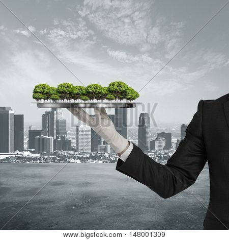 Businessman hand in glove holding silver tray with abstract trees on city background. Growth and development concept