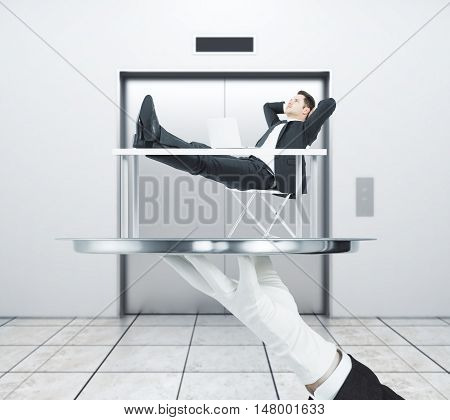 Hand in glove holding abstract silver tray with relaxing businessman. Elevator in the background