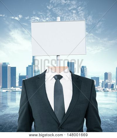 Young businessman body with white signboard instead of head on city background. Mock up